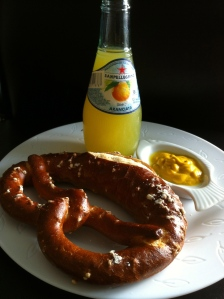 Orangina with a soft pretzel and cheap yellow mustard
